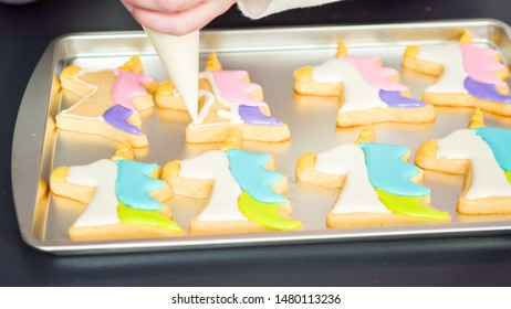 Decorating unicorn sugar cookies with multi-color royal icing.