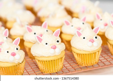 Decorating vanilla cupcakes with a white buttercream icing and bunny ears for Easter.