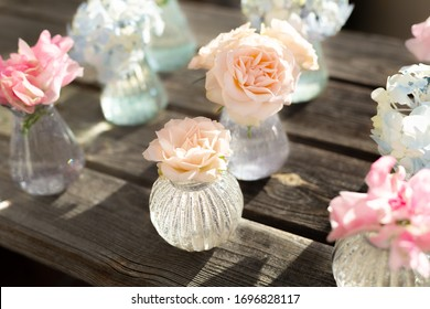 Decoration of blooming blue hydrangea, sweet pea Lathyrus, bush roses in small crystal vases on wooden background. Design,creative.International Women's Day,March 8 and Valentine's Day,14 of February.