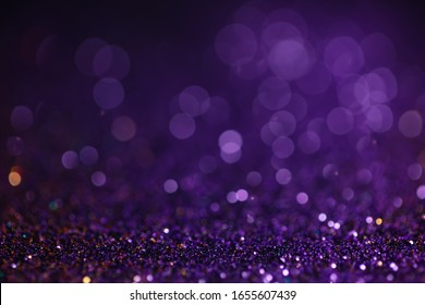 Decoration bokeh glitters background, abstract glowing backdrop with circles,modern design wallpaper with sparkling glimmers. Black, purple and golden backdrop glittering sparks with glow effect