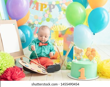 decoration for boy's first birthday, smash cake in a art painter style. baby smiling looking at camera. Portrait of adorable caucasian baby boy celebratingsitting on wooden floor in studio.