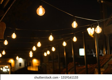Decoration of the cafeteria. Edison incandescent lamps. Street decor Light lanterns Warm light at night. The web is in the middle of the light bulb. Macro shooting bulbs.