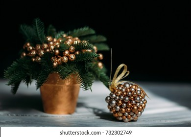 decoration of Christmas tree branches with Golden balls in the Golden pot, near the Golden ball of beads, white countertop, even, background, white vintage table