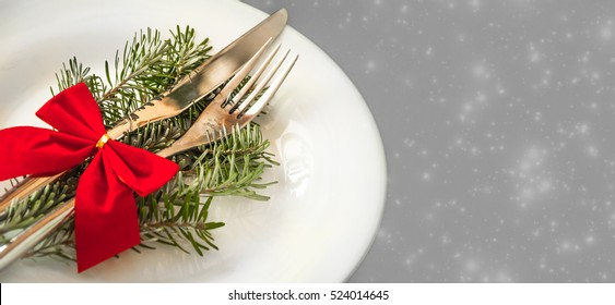Decoration of a festive table. Cutlery on a white plate with a branch of a Christmas tree and red bow. Panoramic photo