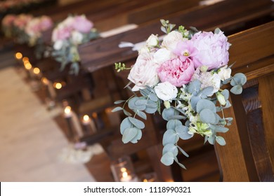 Decoration from flowers in the church. Peonies, bows, candles, church hall