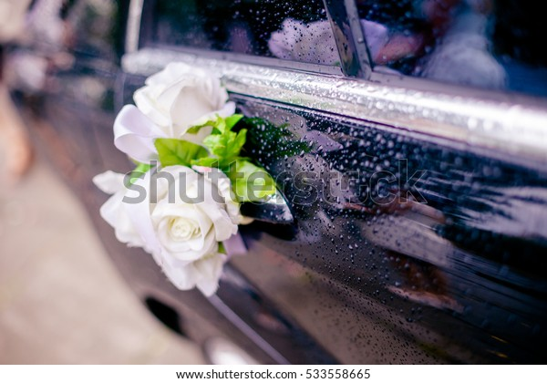 Decoration of flowers roses on the door handle of the car covered with drops of rain on your wedding day