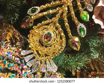 Decoration in the form of a feather of a bird of a peacock or a feather of a Firebird of gold color with multi-colored rhinestones and stones on a new year tree.