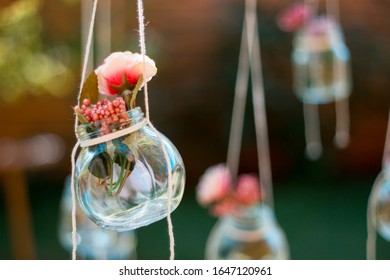 Decoration glass jar with flowers hanging with blur garden background. Soft focus