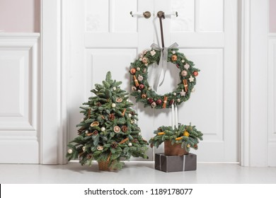 Decoration of the house before the new year holidays. Set of decorative elements with fir branches wreath, Christmas tree and arrangement in a wooden box