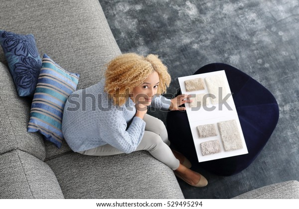Decoration of houses. Woman chooses carpet picker sitting on the sofa in the living room