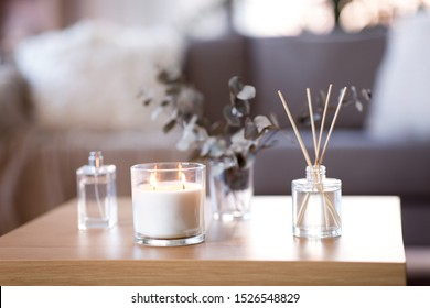 decoration, hygge and aromatherapy concept - aroma reed diffuser, burning candle, branches of eucalyptus populus and perfume on table at home - Shutterstock ID 1526548829
