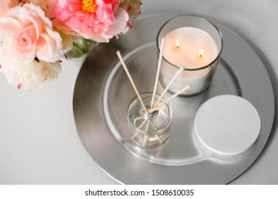 decoration, hygge and cosiness concept - aroma reed diffuser, burning candle and flower bunch on wooden table
