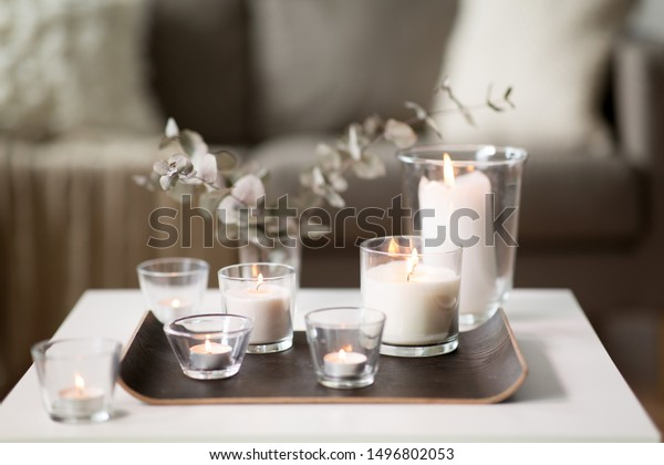 decoration, hygge and cosiness concept - burning white fragrance candles on tray and branches of eucalyptus populus on table at cozy home