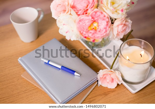 decoration, hygge and cosiness concept - burning fragrance candle, flower bunch, books and pen on wooden table