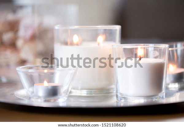 decoration, hygge and cosiness concept - burning white fragrance candles on tray on table