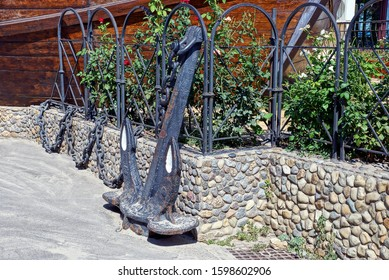 decoration from an old black iron anchor on a chain on the street on a gray sidewalk near a stone fence with green vegetation