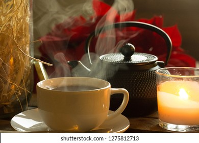 Decoration setup. Hot cup of tea / coffee, smoke, warm. With a rustic teapot, a natural decorative element and the light of a candel. Some red flowers / roses in the background.