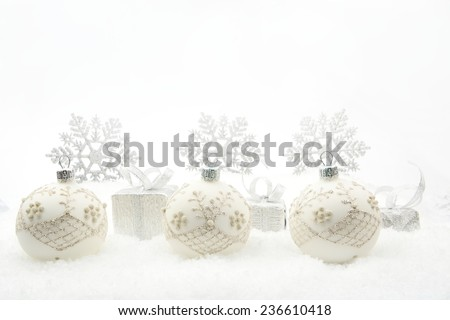 f095661da0211 Decoration of silver christmas gifts and baubles and snowflakes on snow on white  background