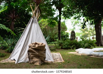 Decoration small tipi indian tent with pillows in the woods