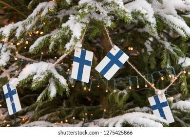 Decoration of a snow-covered Christmas tree of garlands and Finnish flags