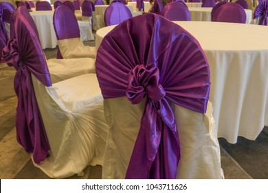 Decoration of tables and chairs in a hotel interior. Whtie and purple or violet textile
