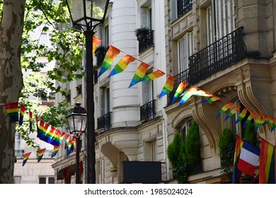 Decoration of triangle shape banners in colors of Lgbtq flags hanging between vintage lantern streetlights and ornate house with balconies. Gay pride parade symbols and French flag in Paris, France - Shutterstock ID 1985024024