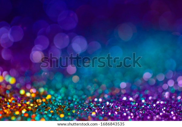 Decoration twinkle lights background, abstract blurred backdrop with circles,modern design overlay with sparkling glimmers. Blue, purple, golden and green backdrop glittering sparks with glow effect