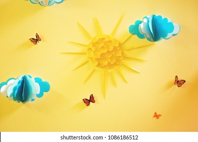 The decoration of the wall in the nursery with paper clouds, sun and butterflies