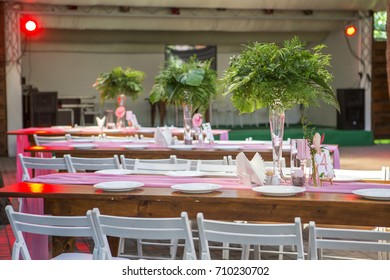 Decoration for a wedding ceremony on a back yard with tables, plates, and vases full of anthurium flowers and monstera leafs. Pink and green colors. Space for text