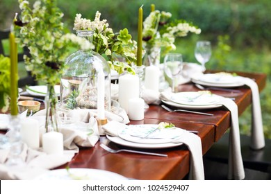 Decoration of wedding table with crystal vases, flowers and branches in botanical style in the garden