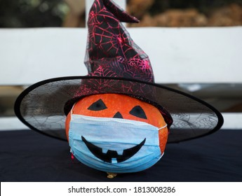Decorations for Halloween in new reality of  covid-19 pandemic. pumpkins in  witch hat and  medical mask with  scary smile painted on it