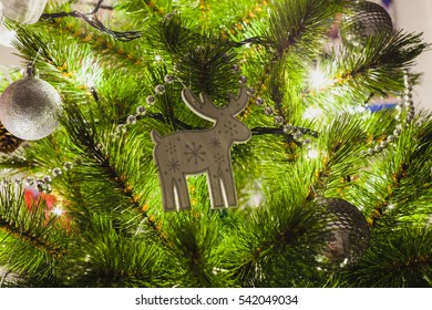 decorations on an artificial green christmas pine tree at home