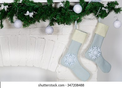 Decorations on the Christmas fireplace in the form of Christmas wreath and socks for Christmas gifts