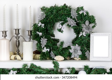 Decorations on the Christmas fireplace in the form of candlesticks, Christmas wreath and photo frames