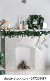 Decorations on the Christmas fireplace in the form of candlesticks, Christmas wreath and photo frames, socks for Christmas gifts
