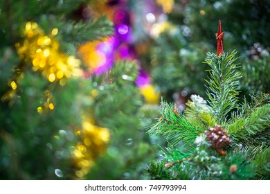 Decorations on christmas tree at night with bokeh on background, soft focus