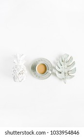 Decorations: pineapple, coffee, monstera palm leaf on white background. Flat lay, top view blog hero header.