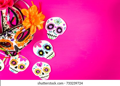 Decorations for traditional Mexican holiday Day of the Dead on a pink background.