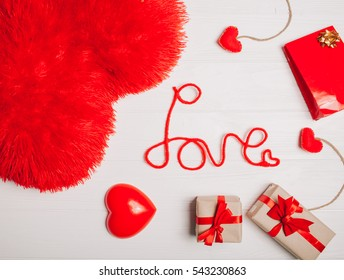 """decorations for Valentine's Day. gifts, heart and the words """"Love"""" on white wooden background"""
