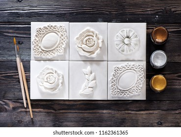 Decorations white plaster relief stucco, brushes for drawing and wax for patina, flat lay