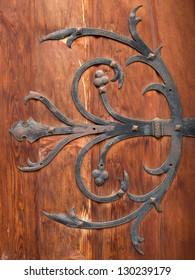 Decorative abstract flower iron hinge of an ancient wooden door