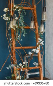 Decorative antique edison style light bulbs against wooden ladder background. lights on the background of blue wall