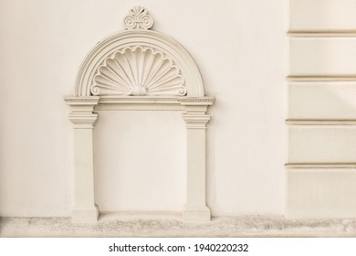 Decorative arch and semi vault above niche with classic pillars. Architectural stucco detail of old European buildingin Prague. Elegant masonry facade decor in beige color. No people, front view. - Shutterstock ID 1940220232