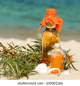 Decorative arrangement of sea buckthorn products, twigs and berries on sandy beach; Healthy natural sallow thorn products; Typical fruit at North German's coasts