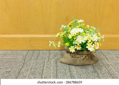 Decorative artificial flowers in brown sack on carpet and wood background