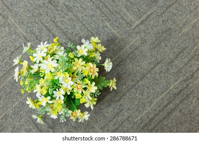 Decorative artificial flowers on carpet background