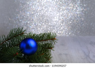 Decorative background with fir branches and blue balls on the silver. Christmas card Holiday Concept