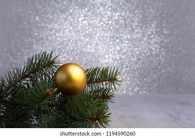 Decorative background with fir branches and gold balls on the silver. Christmas card Holiday Concept