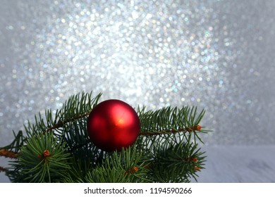 Decorative background with fir branches and red balls on the silver. Christmas card Holiday Concept