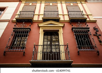 Decorative balconies and windows with gates of old city center house in Seville, Spain